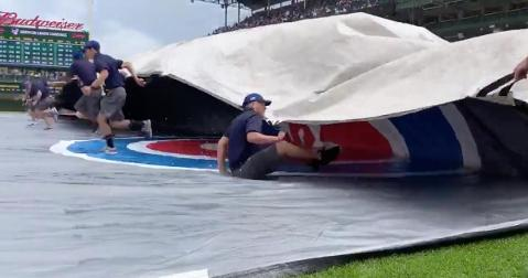 """Giving new meaning to """"slip-and-slide,"""" this unlucky grounds-crew employee was engulfed by the Wrigley Field tarp."""