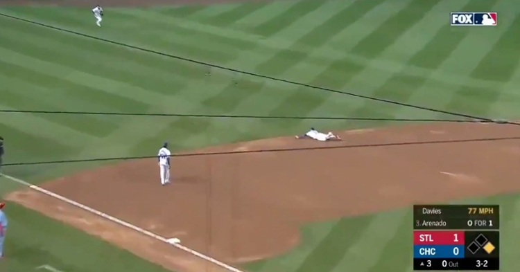 Javier Baez dived onto the infield dirt in order to snag a ground ball hit by Nolan Arenado.