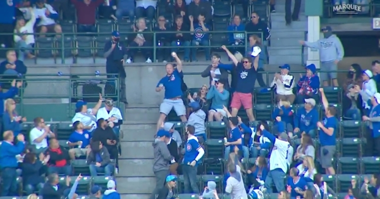 A Cubs fan corralled a foul ball with his left hand while holding a cup of beer in his right hand, but not a drop of beer was spilled.