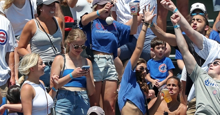 Unaware of the projectile heading toward her, a fan nearly paid the price for staring at her phone in the midst of a Cubs game. (Credit: John J. Kim/Chicago Tribune)