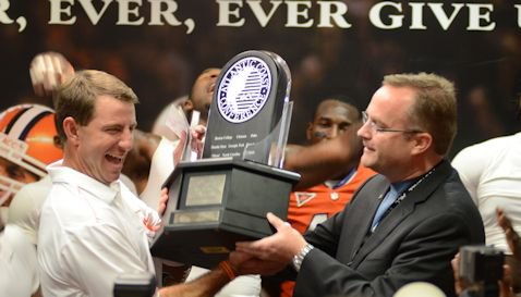 Head Coach Dabo Swinney accepts the Atlantic Division trophy from ACC Associate Commissioner Michael Kelly in the Clemson lockerroom. (Photo: Zach Hanby)