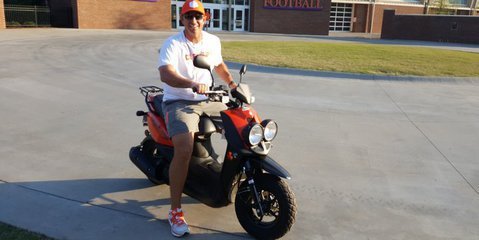 Swinney can be seen driving cars, mopeds, and golf carts on campus