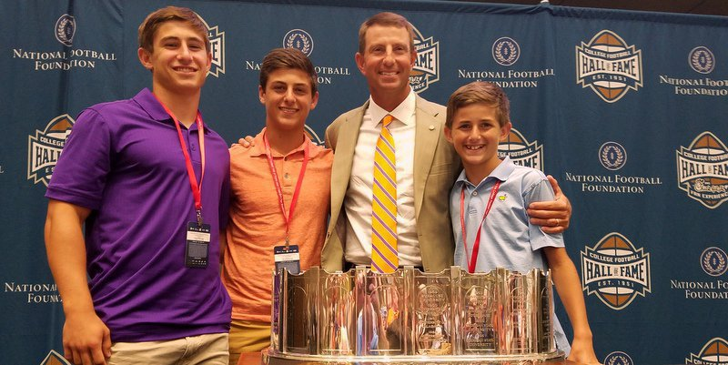 Swinney poses with his sons and just one of the many trophies he's helped win