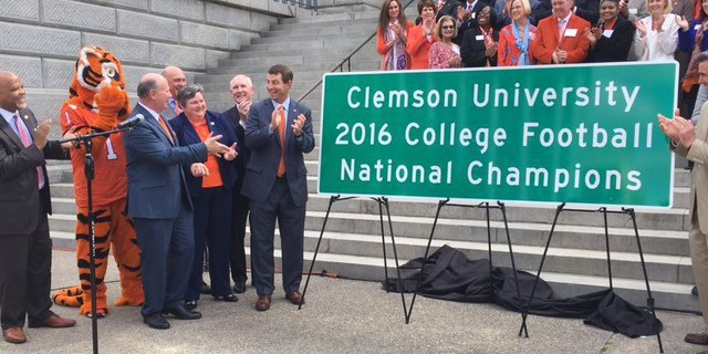 Swinney poses with one of the new signs honoring the National Championship  (Photo by Jared Rogers-Martin)
