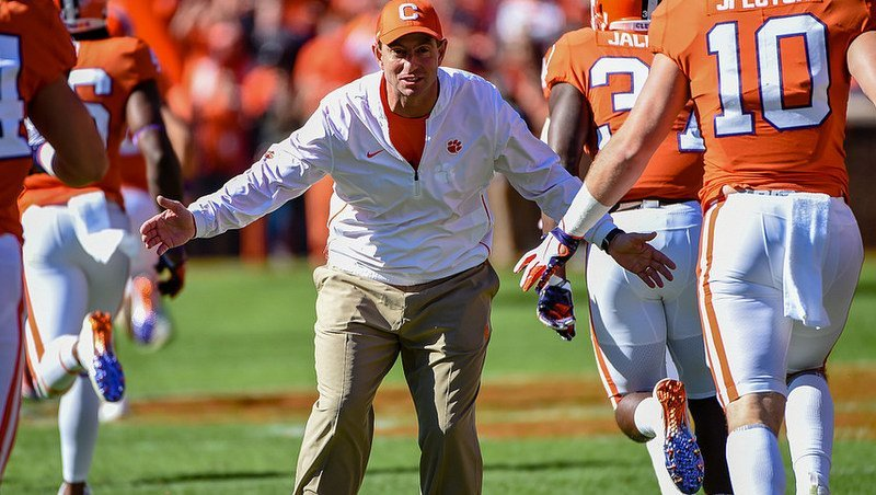 Swinney greets his players after running down the hill Saturday