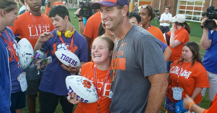 Dabo Swinney poses with a student after practice Wednesday.