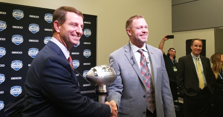 Swinney and Mendenhall shake hands in front of the ACC Championship Trophy.