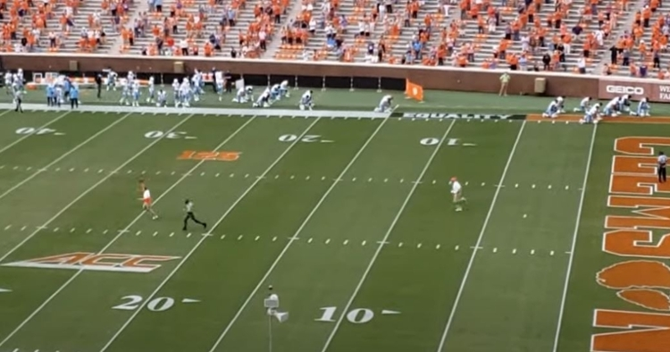 Swinney and the Highway Patrol officer race each other onto the field.